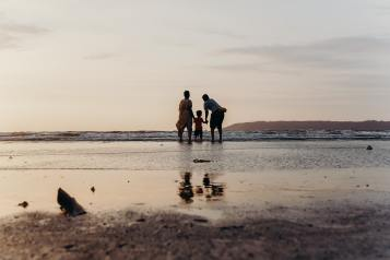 photo-of-three-people-standing-on-beach-4430312